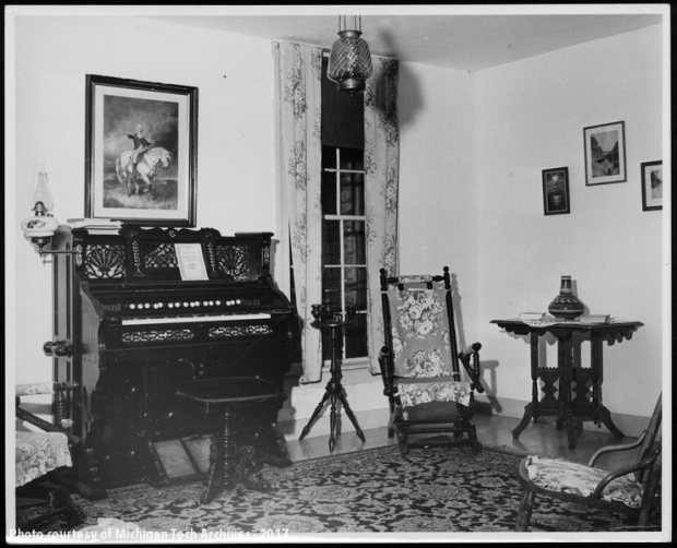 Image of parlor with organ and furniture.