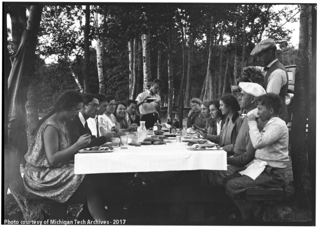 Group of people gathered around a long picnic table with a white cloth