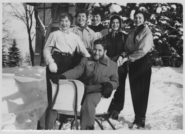 The 1955 Carnival Queen candidates pose outside with a young man in a sled.