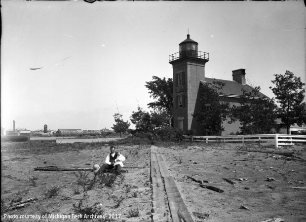 Man sitting with child on beach before lighthouse