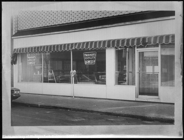 Image of storefront with awning and signs