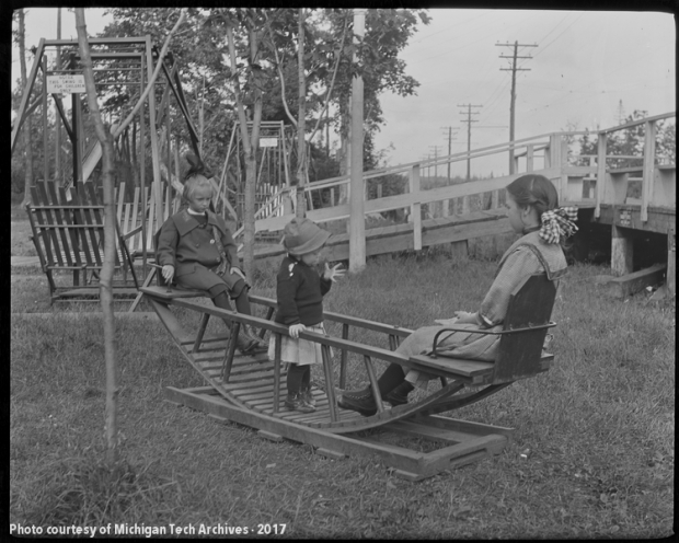 Three children on a rocking wooden swing