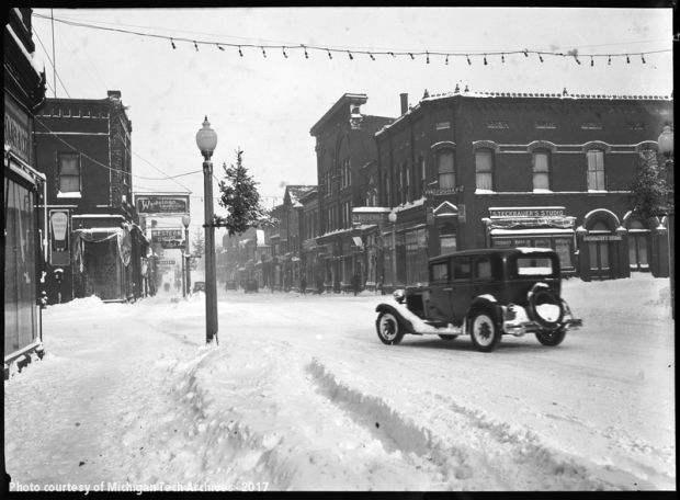 Snow-covered street in town with old car