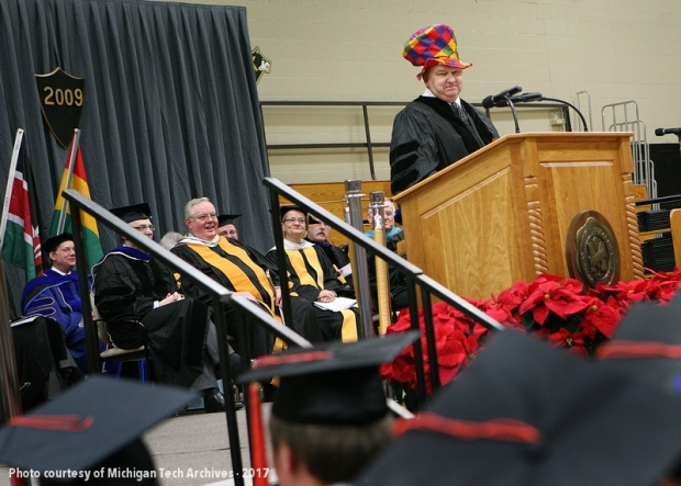 Man in multicolored hat at graduation podium