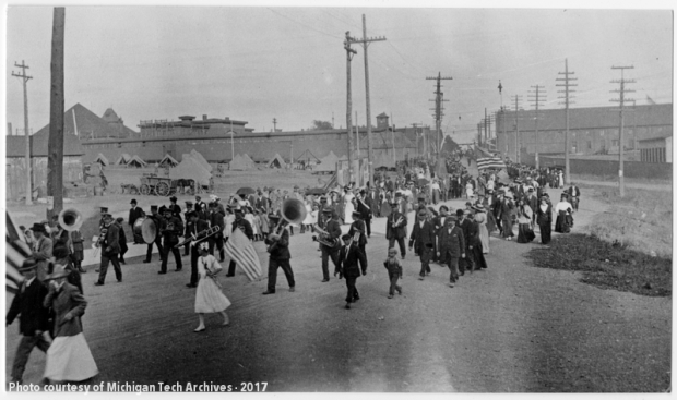 Group of men, women, and children marching with American flags
