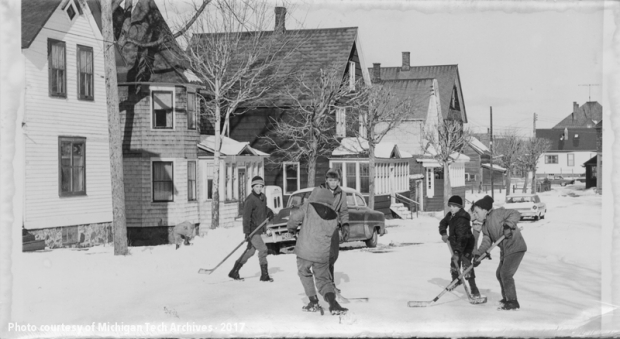 Group of boys playing hockey on a snowy residential street