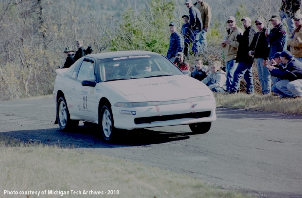 Image of a rally car driving by some spectators.