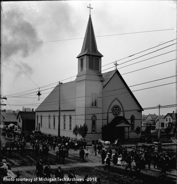 Wood-frame church surrounded by people on a dirt road
