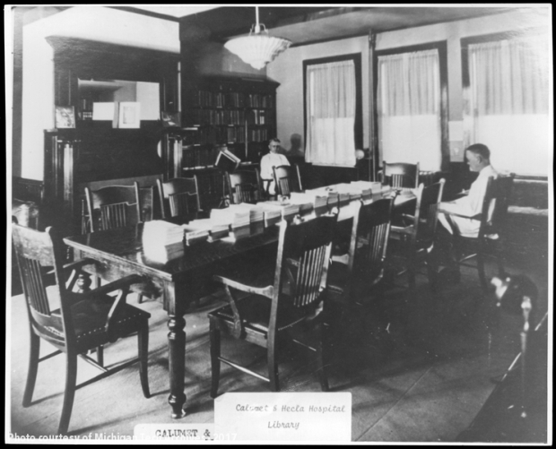 Two men seated near long table in library