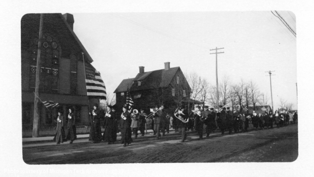Big Annie carries a large flag during a strikers parade during the 1913-1914 copper miners' strike.