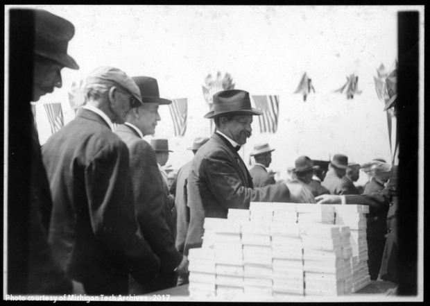 Men in suits lined up to receive small boxes