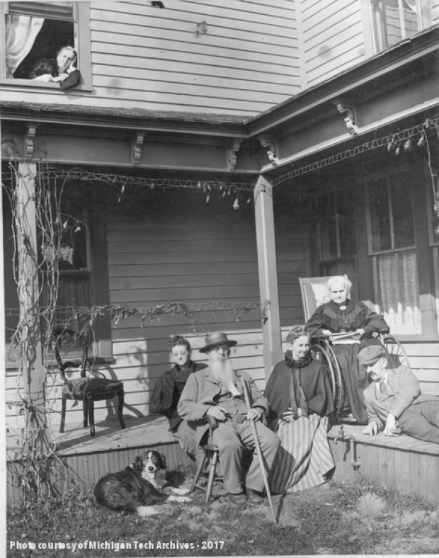 Group of people of various ages, and their dog, on the porch of a house