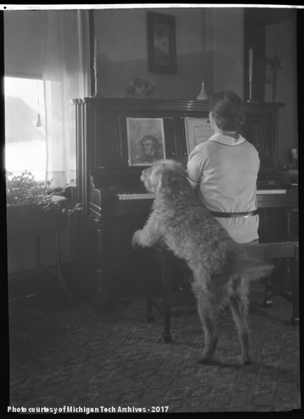 Woman in white playing a piano with a dog resting his front paws on her bench